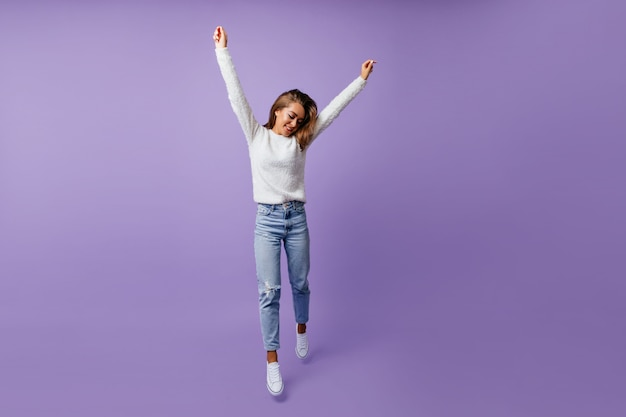 Cheerful student in good mood happily jumping. long-haired brown-haired woman in stylish jeans and white sneakers poses for full-length portrait