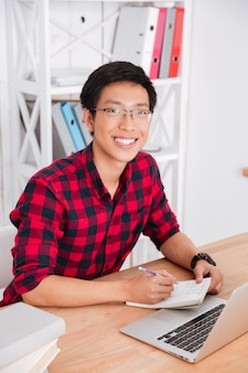 Cheerful student looking at front and working at him laptop in classroom. sitting near books. writing notes in notebook