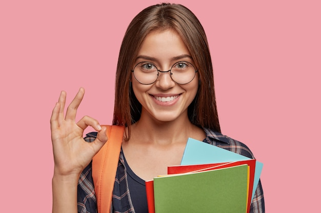 Веселый студент позирует на розовой стене в очках