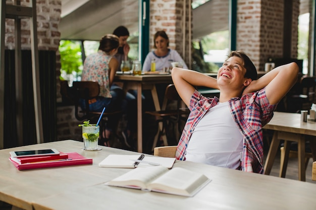 Cheerful student relaxing at table