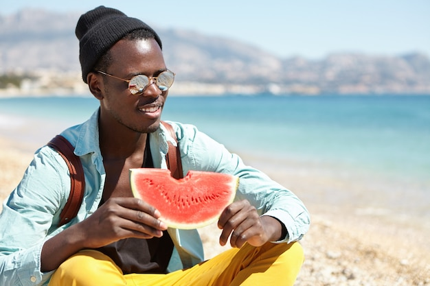 Cheerful student sitting cross-legged on pebble beach and eating fresh juice watermelon