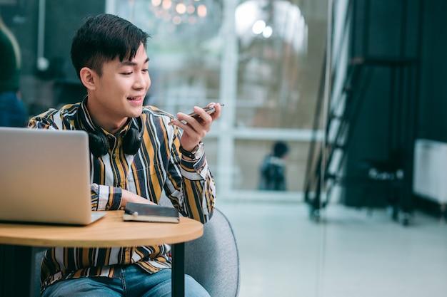Веселый студент сидит перед ноутбуком и улыбается, держа смартфон и отправляя голосовые сообщения. баннер веб-сайта