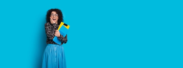 Cheerful  student with curly hair surprised by something while posing on a blue wall with free space
