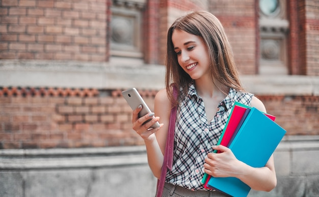 A cheerful student with multicolored notebooks dials a message on the phone near the campus walls