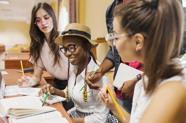 Веселые студенты сидят за столом и учатся