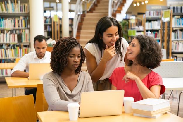 Веселые студенты работают над новым проектом в библиотеке