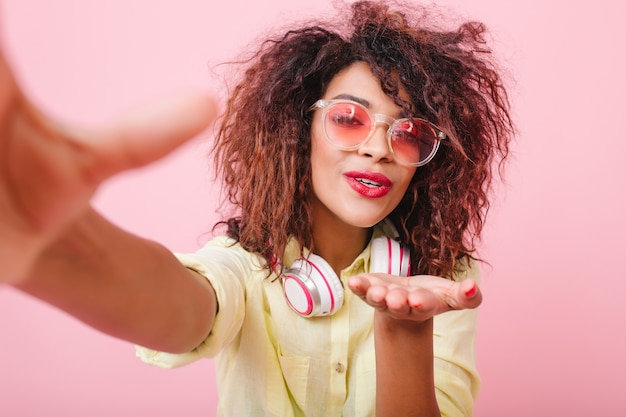 Cheerful stylish african girl wears cute sunglasses sending air kiss while making selfie at home. portrait of happy mulatto lady in yellow enjoying good day and taking picture of herself.