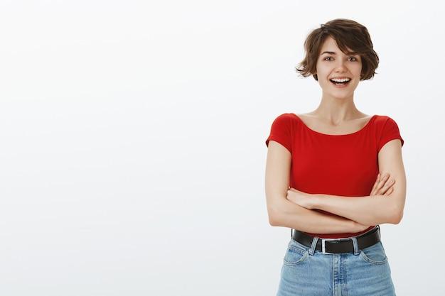 カメラで幸せそうに笑っている陽気なスタイリッシュな女の子