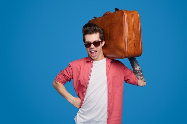 Веселый стильный мужчина с чемоданом
