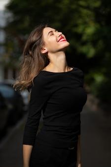 夏に通りを歩く古典的な黒い服を着た陽気なスタイリッシュな女性