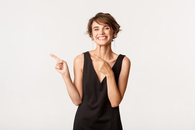 왼쪽 손가락, 로고 표시 및 행복 미소를 가리키는 검은 드레스에 쾌활 한 세련 된 여자.