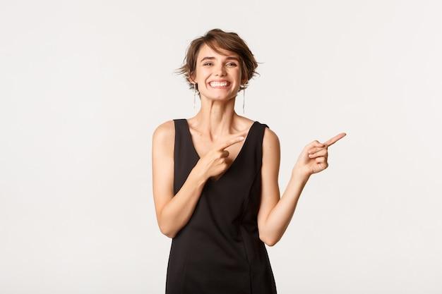오른쪽 손가락을 가리키는 검은 드레스에 쾌활 한 세련 된 여자, 로고를 표시 하 고 행복 하 게 웃 고.