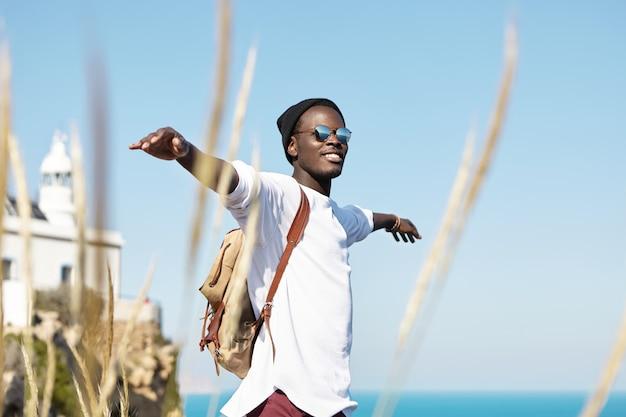 陽気なスタイリッシュな若いアフリカ系アメリカ人旅行者は、バックパックを嬉しそうに笑って、腕を広げて、自由に、幸せでリラックスして、海辺で週末を海外で過ごしながら素敵な夏の日を楽しんでいます。