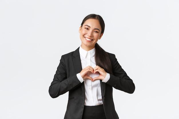 彼女のクライアントの世話をし、心のジェスチャーを示し、幸せな笑顔を見せ、顧客に思いやりのあるサービスを提供し、白い背景に立って、黒のスーツで陽気な成功したアジアの実業家