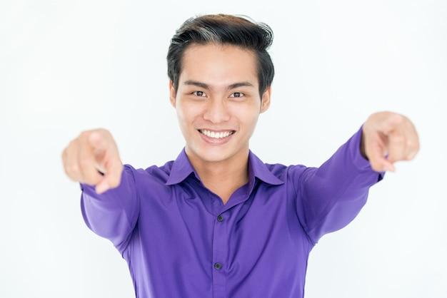 Allegro uomo asiatico di successo che punta alla macchina fotografica