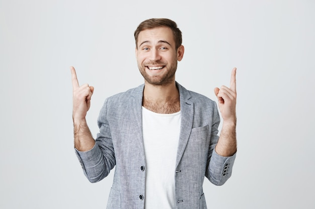 Cheerful successful businessman pointing up