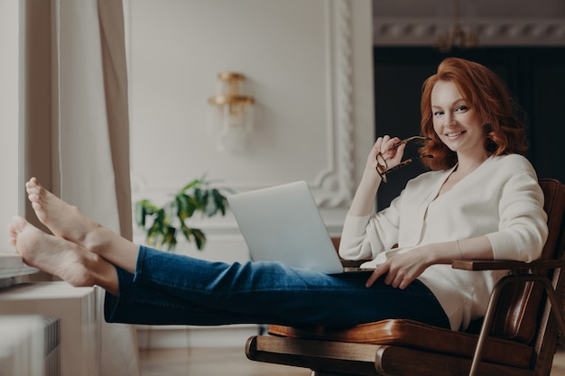 Cheerful successful ginger woman copywriter works from home, keeps laptop on knees