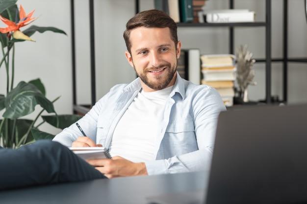 Веселый успешный молодой человек в повседневной одежде, использующий ноутбук для онлайн-конференции на рабочем месте или дома, держит ноги на столе
