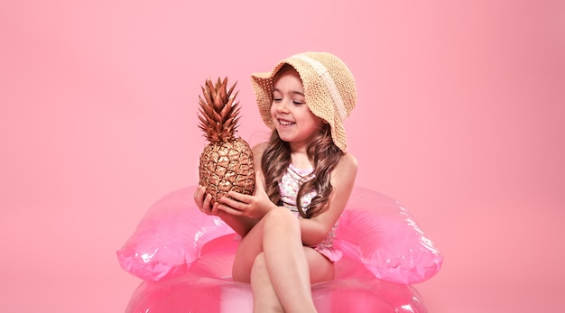 Веселая летняя девушка с ананасом на цветном фоне