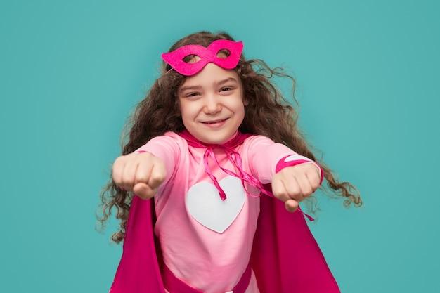 陽気なスーパーヒーローの子の女の子が飛んでいます