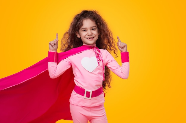 ピンクの衣装で陽気なスーパーヒーローの子供の女の子