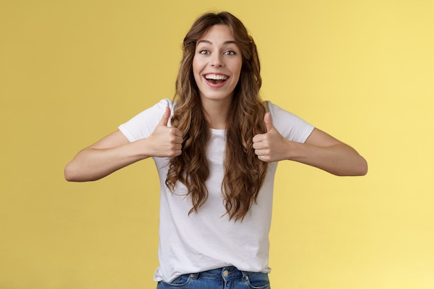 Cheerful suportive energized cute european cute curly-haired girl show thumbs-up approval rooting for friend excellent effort nodding accepting great awesome work done stand yellow background