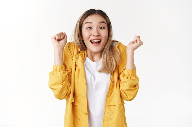 Cheerful supportive attractive silly asian blond girl triumphing raise clenched fists joyful smiling broadly cheering supportive awesome news feel winner celebrating victory good news