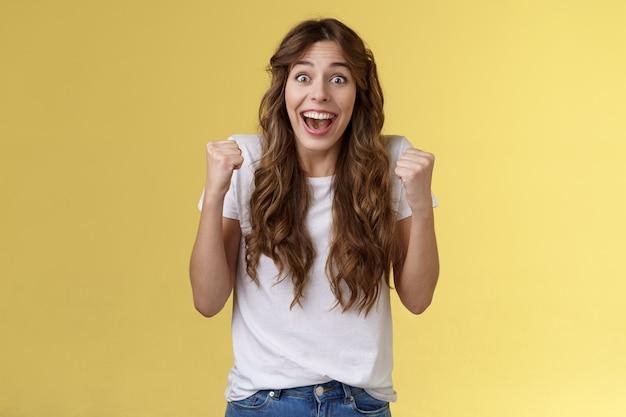Allegro solidale felice divertimento femminile pompa pugno sollevato trionfante tifo tifo per la squadra preferita vincente sorridente ampiamente si spera guardare fotocamera celebrando vittoria sfondo giallo