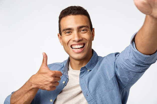Cheerful supportive man holding device with stretched hand