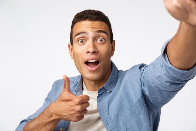 Веселый поддерживающий мужчина держит устройство с протянутой рукой
