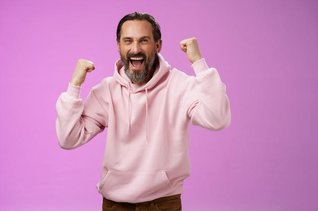Cheerful supportive manly mature adult bearded guy fan yelling raising clenched fists triumphing team scored goal celebrating standing pleased shouting achieving success, posing purple background.
