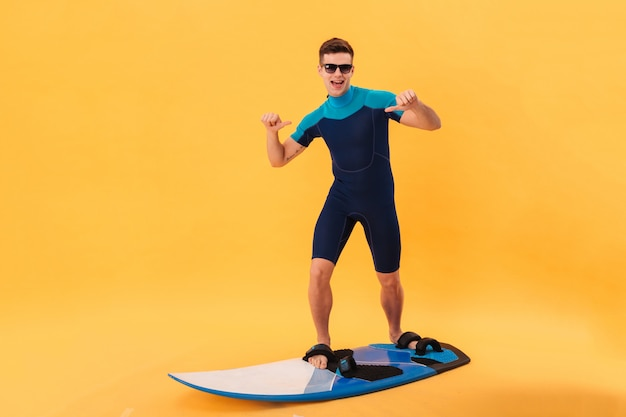 Cheerful surfer in wetsuit and sunglasses using surfboard indicates itself and looking at the camera
