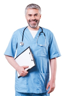 Cheerful surgeon. cheerful mature doctor looking at camera and smiling while holding clipboard and standing isolated on white