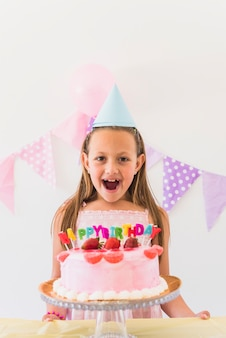 Cheerful surprised birthday girl standing behind cake and candles