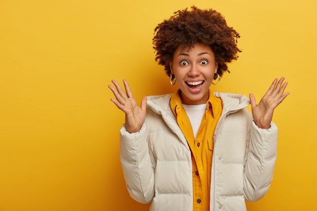 Cheerful surprised dark skinned woman raises palms, happy to get nice present, wears white warm winter coat, yellow jacket, expresses good emotions, smiles broadly, has happy reaction on surprise