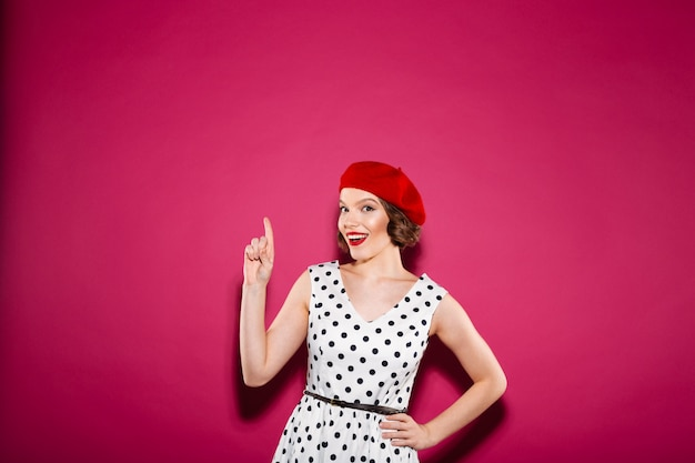 Cheerful surprised ginger woman in dress with arm on hip pointing up and looking at the camera over pink