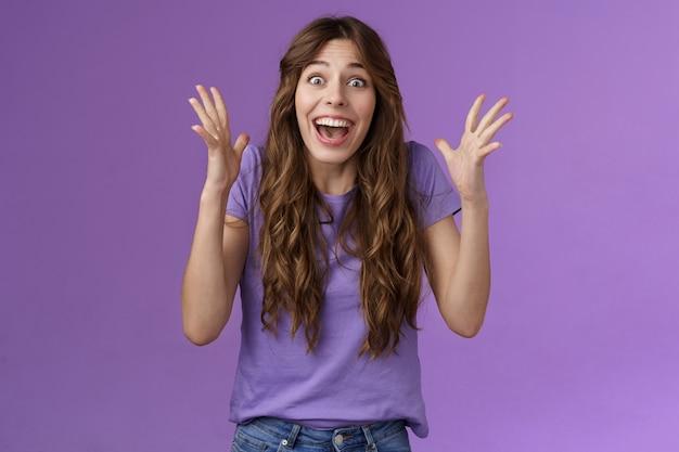 Веселая удивленная счастливая девушка получает невероятный суперприз, торжествуя, радостно улыбается, пожимает руку, волнение, радость, празднует прекрасные новости, счастливо улыбается победа, фиолетовый фон