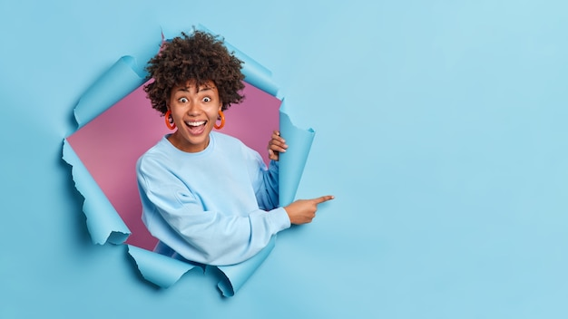 Cheerful surprised woman breaks through paper wall demonstrates copy space aganst blue wall gives advice shows advertisement on empty space wears casual sweater and earrings