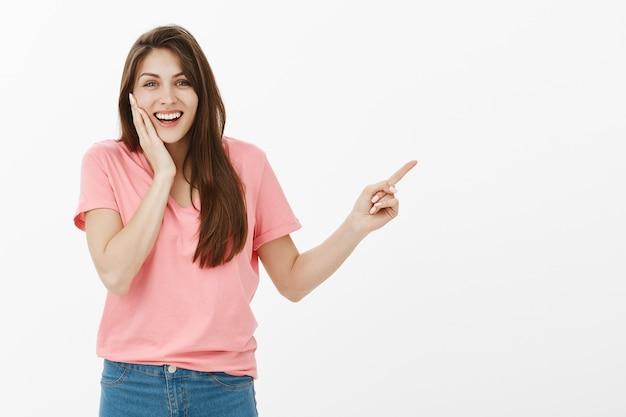 Веселая удивленная женщина указывает верхний правый угол и чувствует себя счастливой
