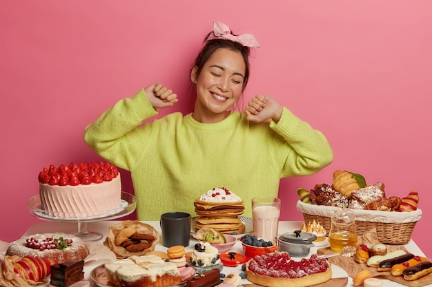 Cheerful sweet tooth girl stretches with pleasure, surrounded by bakery production, comes on festive event, feels satiety, wears green jumper, isolated on pink wall has toothy smile.