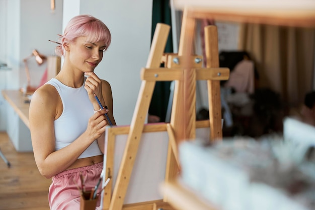 Cheerful talented woman thinks sitting at easel with canvas in studio