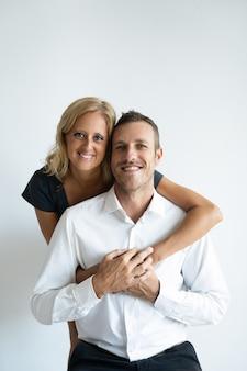 Cheerful tanned woman hugging handsome boyfriend in white shirt.