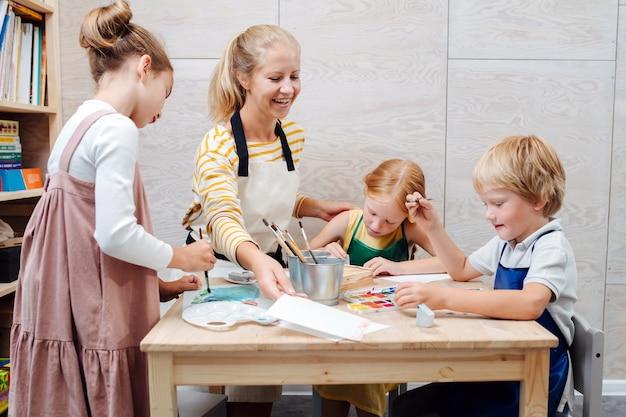 プロセスに浸された水彩画で子供たちがペイントするのを助ける陽気な先生