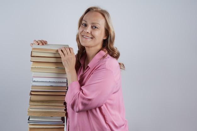 분홍색 블라우스에 쾌활한 교사는 책 초상화의 큰 더미 옆에 서