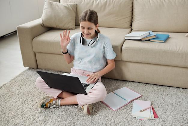 自己隔離中に家にいる間、ビデオチャットを介して友人と通信するカジュアルウェアの陽気なティーンエイジャー