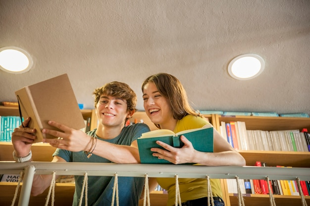Cheerful teen couple studying in library