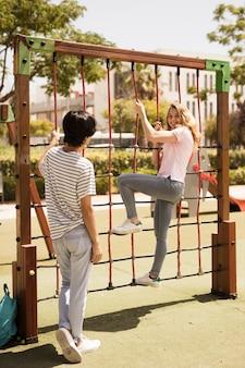 Cheerful teen friends on climbing net on playground