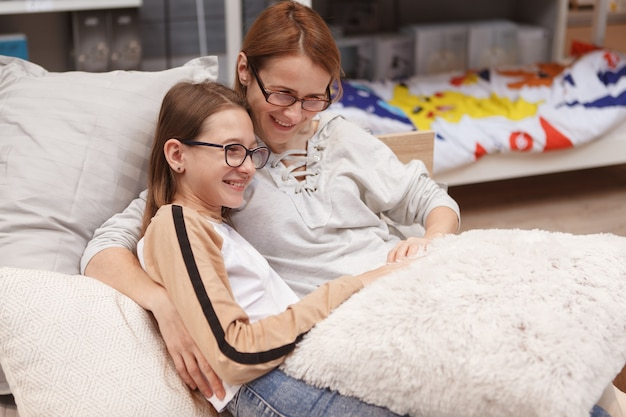 Cheerful teen girl enjoying cuddling with her mom on a bed at furniture store