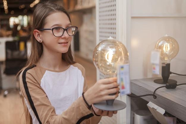 電球ランプを持って、日用品店で買い物をする陽気な十代の少女