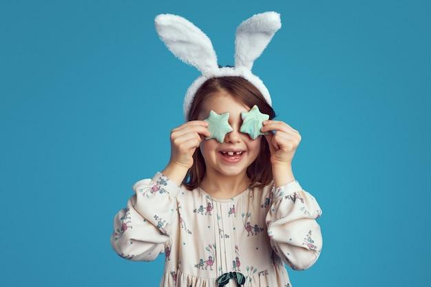 Веселая девочка-подросток улыбается и закрывает глаза печеньем в форме звезды